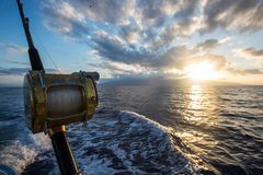 Deep Sea Fishing Reel on a boat during sunrise royalty free stock images