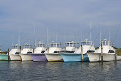 Deep sea fishing boats. Row of multi-colored nice deep sea fishing boats in a marina Royalty Free Stock Photo
