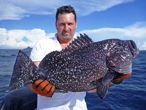 Deep sea fishing. grouper fish. Fishermen holding a giant grouper Royalty Free Stock Photography