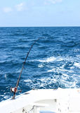 Deep Sea Fishing. A fishing rod set to troll behind the boat in the ocean royalty free stock photo