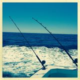 Deep sea fishing. Fishing by rods and line  from the back of a small boat surrounded by blue ocean and sky Royalty Free Stock Photo