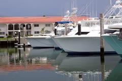 Deep Sea Fishing Yachts. Some deep sea fishing yachts tied up in a mrina nead a condo Stock Photo