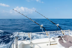 Deep sea sport fishing with rods an reels. Sport fishing with two salt water rods and reels. Deep sea fishing in the ocean on a sunny blue sky day with fluffy royalty free stock images