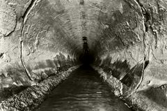 Deep sewage tunnel with poinson flowing Royalty Free Stock Image