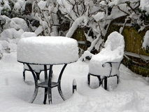 Deep snow covers garden table, chairs and plants. Deep snow covers cast iron garden table, chairs and plants, Buckinghamshire, UK Royalty Free Stock Photography
