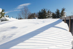 Deep snow in drifts on deck in back yard Royalty Free Stock Image