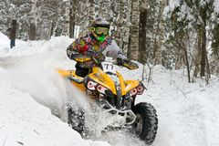 Deep snow is not a hindrance. MOSCOW, RUSSIA - FEBRUARY 10, 2018: Sports quad bike rushes on the snow-covered road in the forest. Russian Outpost Winter 2018 royalty free stock photo
