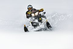 In deep snowdrift snowmobile rider make fast turn. Riding with fun in deep snow powder during backcountry tour. Extreme sport