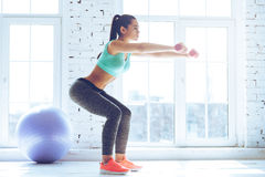 Deep squat. Side view of young beautiful woman in sportswear doing squat and holding dumbbells while standing in front of window at gym Royalty Free Stock Images