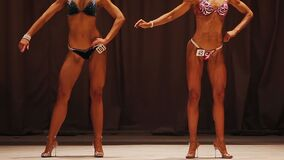Deep tanned female bodybuilders competing in sport contest, ideal bodies