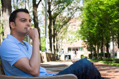 Deep thinker. Closeup portrait, young man in blue shirt, sitting, thinking deeply, daydreaming, sunny outdoors, trees background. Human emotions facial Stock Images