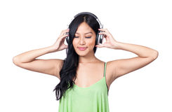 Deep in thought. A young Asian girl relaxed while listening to sounds through headphones Stock Photo