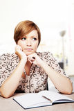Deep in thought. Woman at a desk deep in thought stock photo