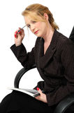 Deep in thought. Business woman with pen to her head, bent over her report looks at you as she is lost deep in thought for ideas Royalty Free Stock Images