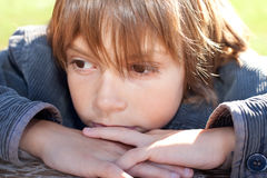 Deep in thoughts. Close up portrait of a little boy deep in thoughts Royalty Free Stock Photo