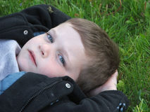 Deep Thoughts in the Grass. Young boy with inscrutable expression on his face, lying in the grass, close up stock images