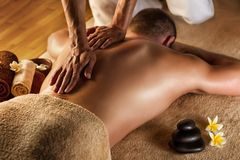 Deep tissue massage. Man has deep tissue massage on the back. Spa stones and frangipani flowers