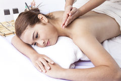 Deep tissue massage therapy in spa. Massage therapist's healing hands work on shoulders of woman to relieve stress Royalty Free Stock Images