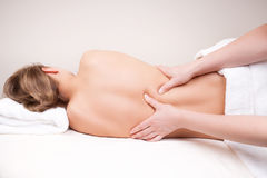 Deep tissue massage on the woman's middle back. On erector spinae muscles Stock Image