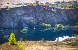 Deep unused stone quarry and the river Stock Image