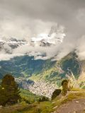 Deep valley below autumn misty peaks of Alps mountains in background. Small mountain town under mist cover. Stock Photo