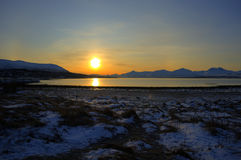 Golden sunrise over blue fjord and snowy mountain with reflection on thick ice. Deep vibrant golden sunrise over fjord and snowy mountain landscape with Royalty Free Stock Photography