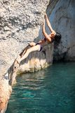 Deep water soloing, young female rock climber on cliff Royalty Free Stock Photos