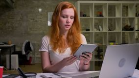 Deeplu concentrou o gengibre que a fêmea caucasiano swiping sua tabuleta ao sentar o frio em seu desktop no escritório do moder filme