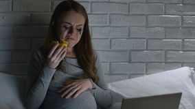 Deeply crying pregnant woman eating donut in front of laptop at night, problems stock video footage