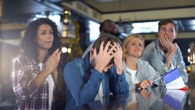 Deeply unhappy french football fans with flag, watching sports program in bar. Stock photo stock photo