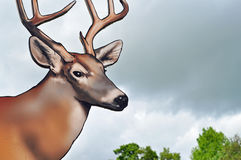 Deer with antlers wooden sign. A deer with antlers made out of wood on a sign set against a darkening sky Royalty Free Stock Photos