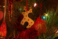 Deer on Christmas tree. Reindeer Christmas toy on Christmas tree prickly green pine wooden toy New Year holiday tradition deer Stock Photo