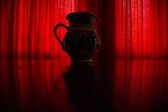 Red curtain low light art vase Stock Images