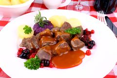 Deer goulash with potato, Burgundy sauce and wild berries Stock Image
