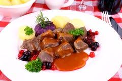 Deer goulash with potato, Burgundy sauce and wild berries Stock Image