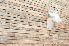 Deer head made of paper on a wall of wooden slats. View at an angle. Designer background for decoration in the room. Christmas wal stock image