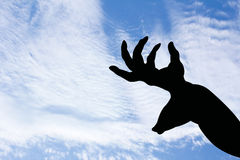 Deer with horn shape hand silhouette in blue sky. Stock Photo