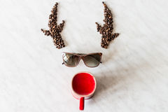 Deer. Horns from coffee beans. Sunglasses. Red cup Royalty Free Stock Image