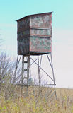 Deer hunters stand. A vertical picture of a wooden camouflaged deer hunters stand in a field with the blue sky behind it Royalty Free Stock Photo