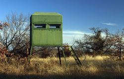 Deer Hunting Stand. Green deer hunting blind or stand,  mesquite tree and oaks in background, dry winter grass and blue sky, winter, late afternoon, north Texas Royalty Free Stock Photo