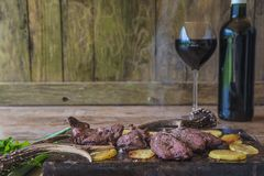 Hunting season meal: deer meat. Deer meat roasted with potatoes and decorated with deer antler and parsleay, bottle and glass of red wine on rustic wooden royalty free stock image