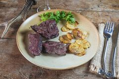 Deer meat roasted with potatoes on the rustic plate, cutlery and deer antler. On the old wooden table stock images