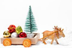 Deer pulling the cart Santa`s sleigh with a mountain of gifts on snow drifts. The concept of approaching family holidays and. Christmas royalty free stock photo