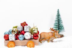 Deer pulling the cart Santa`s sleigh with a mountain of gifts on snow drifts. The concept of approaching family holidays and. Christmas stock image