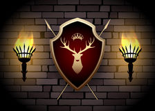 Deer Shield with Torches on the Wall. Coat of arms with torches on the wall. Shield with Deer Head, Crown and two spears behind Stock Photography