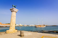 Deer statue with leaving tourist ship in Rhodes harbor Royalty Free Stock Image