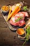Deer or venison roast. Traditional finnish food, rosvopaisti, with Chanterelle fungus, Sea salt, red, green, white pepper and coriander in clay pots on an old Stock Photography
