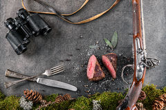 Deer or venison steak with antique long gun, cutlery, binocular and ingredients like sea salt, herbs and pepper, food background f Royalty Free Stock Photos