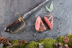 Deer or venison steak with ingredients like sea salt, herbs and pepper and antique saber, food background for restaurant or huntin Royalty Free Stock Photos