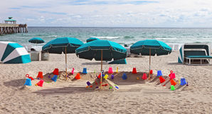 Deerfield Beach. A display of kids toys on the sand with green umbrellas at the Deerfield Beach in Florida Royalty Free Stock Images